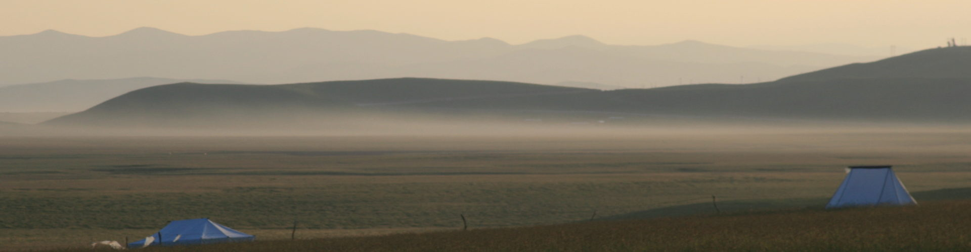 Moutains on the misty horizon beyond a plain